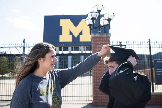 U-M senior Rita Sidhu helps adjust the cap for her friend Brian Galvin before they take graduation photos outside of the Michigan Stadium in Ann Arbor, Tuesday, March 17, 2020.