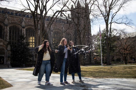 From left, graduating seniors Alex Andrews, Jenna Varcak and Haley Jamieson pop out a bottle of sparkling wine as they pose for a photo for their photographer Hannah Brauer  (not in the photo) in front of Law Library on University of Michigan main campus in Ann Arbor, Tuesday, March 17, 2020.
