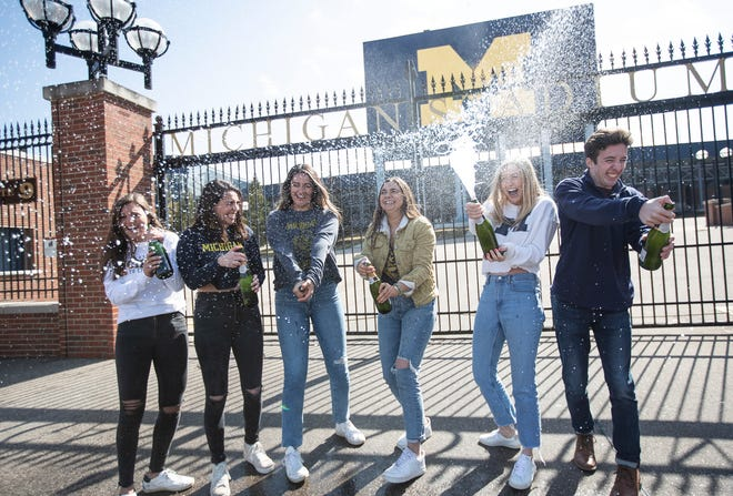 From left, U-M graduating seniors Grace Scarfone, Natalia Engel, Rita Sidhu, Hannah Saunders, Grace Drettmann and Brian Galvin pop bottles of sparkling wine for their graduation photos outside of the Michigan Stadium in Ann Arbor, Tuesday, March 17, 2020.