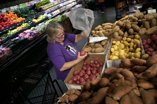 Diane Strauss, 55, of Warren chooses some red potatoes for an online client as she fills grocery orders at Holiday Market in Royal Oak on March 17.