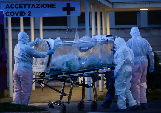 A patient in a biocontainment unit is carried on a stretcher at the Columbus Covid 2 Hospital in Rome, Monday, March 16, 2020.