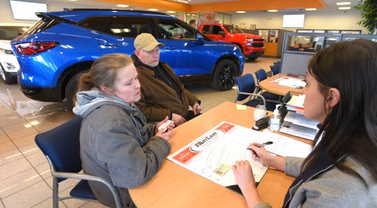 Matthews Hargreaves Chevrolet sales and leasing consultant Jenna Mosser, right, fills out paperwork for Jennifer Creet and her husband, Kerry, both of Troy, as they shop for a used vehicle at Matthews Hargreaves Chevrolet in Royal Oak on Tuesday.