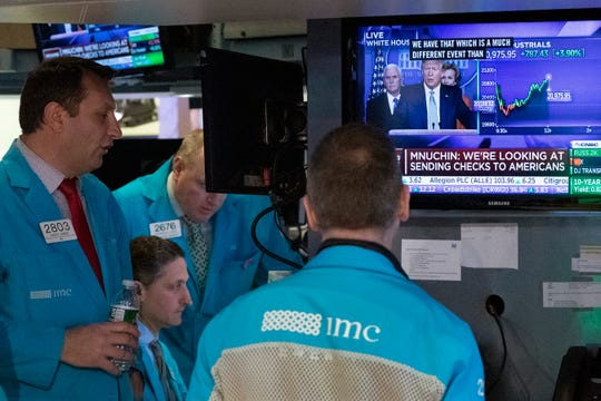 Traders at the New York Stock Exchange listen to President Donald Trump's televised White House news conference, Tuesday in New York.