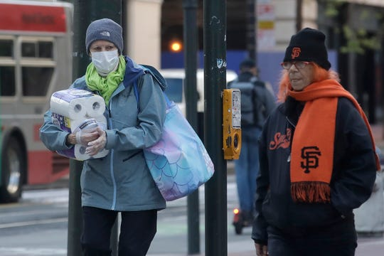 A woman wears a mask and gloves while carrying toilet paper across the street in San Francisco, Tuesday, March 17, 2020.