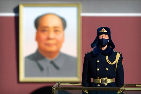 In this Tuesday, Feb. 4, 2020 file photo, a member of an honor guard wears a face mask as he stands guard in Tiananmen Square in Beijing. On Wednesday, March 17, 2020, China announced that it will revoke the media credentials of American journalists at three major U.S. news organizations, in effect expelling them from the country, in response to new U.S. restrictions on Chinese state-controlled media.
