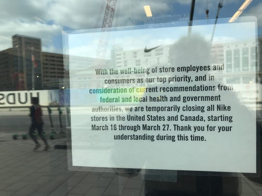 A sign on the door of the Nike store on Woodward explains why their stores are temporarily dark.