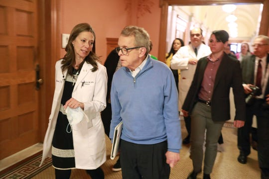 Ohio Department of Health director Amy Acton, left, and Ohio Governor Mike DeWine talk before stepping into a coronavirus news conference Saturday, March 14, 2020 at the Ohio Statehouse in Columbus.