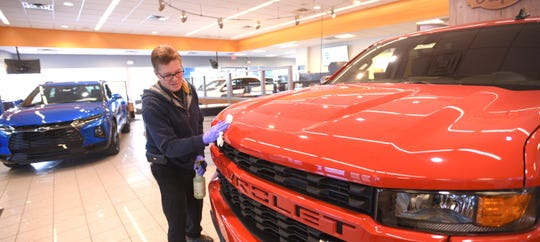 Facilities maintenance employee Barry Cooke, of Madison Heights, wipes down the hood of this 2020 Red Hot Chevy Silverado DBL Custom 4WD pick up truck at Matthews Hargreaves Chevrolet in Royal Oak.