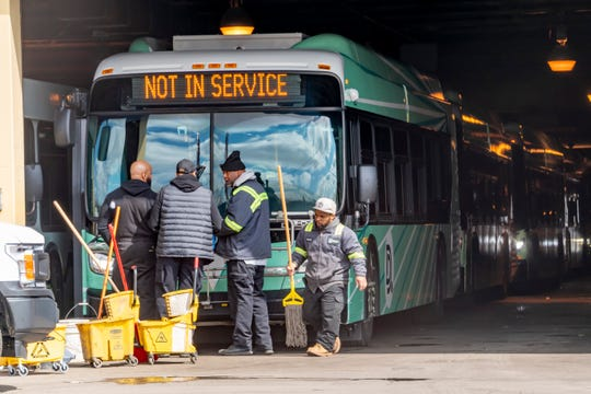 Workers clean the buses at the Detroit Department of Transportation's Gilbert Terminal, in Detroit, March 17, 2020.