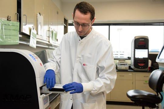 Beaumont medical technologist Michael Diskin runs a COVID-19 test specimen.