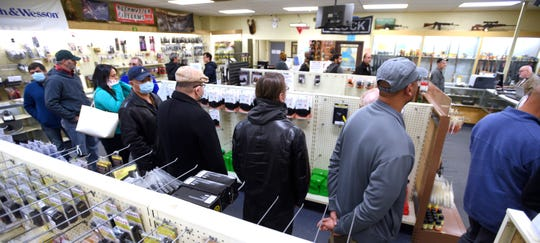 Customers stand in line as they wait to get a federal background check, buy a firearm, ammo or equipment at Double Action Indoor Shooting Center and Gun Shop in Madison Heights.