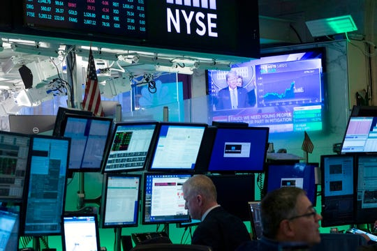 Traders at the New York Stock Exchange listen to President Donald Trump's televised White House news conference, Tuesday, March 17, 2020 in New York.