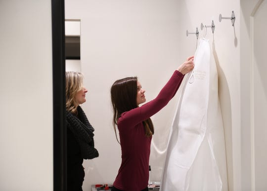 From left, Sales consultant Shawn Vilk watches while Rachel Benefield, 24, of Clinton Township, unzips the bag of her wedding dress at The Wedding Shoppe in Berkley on March 17, 2020. Benefield's wedding is planned for October.