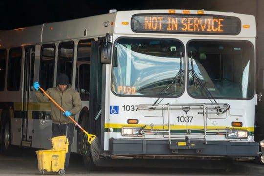 A worker cleans a bus at the Detroit Department of Transportation's Gilbert Terminal, in Detroit, March 17, 2020.