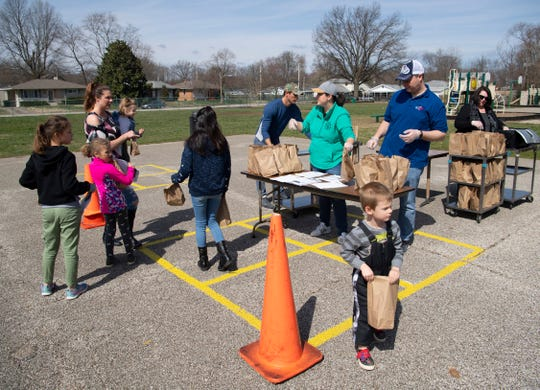 """Zechariah Kemp, 3, bottom right, is loaded up with his """"grab and go"""" lunch and breakfast bags at Caze Elementary School Tuesday morning, March 17, 2020. The Evansville Vanderburgh School Corporation is closed this week due to the coronavirus epidemic and started handing out the meals today and will continue until at least Friday, March 20, 2020. The Christian Fellowship Church and Junior League of Evansville were volunteering to hand out the meals."""