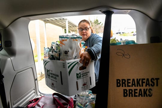 With school suspended because of the coronavirus pandemic, Rebecca Arnett loads boxes of food bags into a van as Henderson County Schools employees distribute free breakfast and lunch meals to anyone 18 years old or younger Monday morning, March 16, 2020.