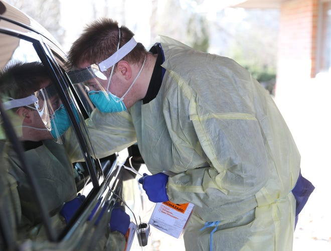Registered Nurse Zach Goiffon administers a COVID-19 test at the drive-thru testing site developed by Marshfield Medical Center-Beaver Dam and Dodge County Public Health Tuesday, March 17, 2020.