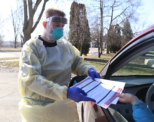 Registered Nurse Zach Goiffon gives post-COVID-19 testing information at the drive-thru testing site developed by Marshfield Medical Center-Beaver Dam and Dodge County Public Health Tuesday.