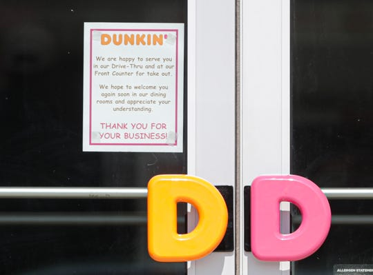A sign on the door of Dunkin' Donuts Tuesday, March 17, 2020, on West Johnson Street in Fond du Lac, Wis., announces the clousure of its dining room to guests during the COVID-19 pandemic affecting the world.