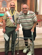 Patrix Heschel and his father Steve stand at St. Boniface Catholic Church after Patrix received the Bronze Pelican Award.