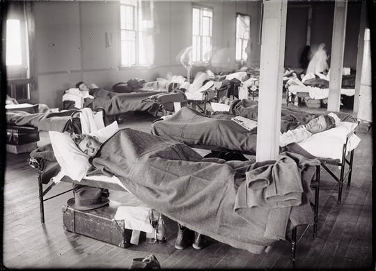 Men rest in makeshift hospital bed on Colorado State University's campus during the 1918-19 influenza epidemic.