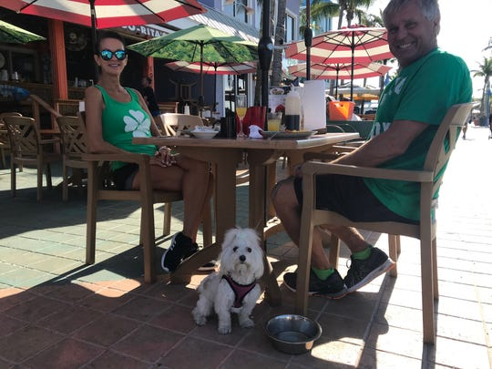 Deb and Tad Delagrade and their dog, Mia, dine at Mango Rita's on Fort Myers Beach Tuesday. The Fort Myers Beach couple said they were not overly worried about the COVID-19  irus.