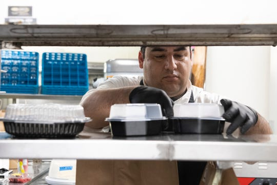 Executive Chef Ramses De La O gathers dishes in to-go boxes for a delivery order at Larkin's Tuesday, Mar. 17, 2020.