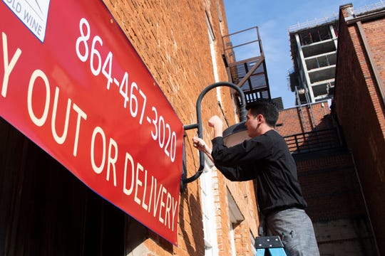 Harry Ustanik hangs a sign outside Larkin's advertising their carry out and delivery options in Greenville Tuesday, Mar. 17, 2020.