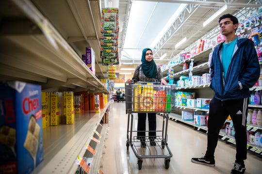 Fareeha Munawar shops for groceries with her son Wajih Qazi at Lowes Foods in Greer, to be donated to Greer Relief & Resources Agency in response to the coronavirus outbreak Tuesday, March 17, 2020.