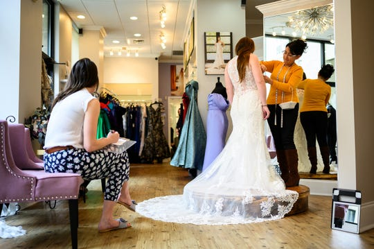 Dorian Santana fits a dress for a customer at The Poinsett Bride Tuesday, March 17, 2020. Many are unsure if they will need to reschedule their upcoming wedding plans due to the spread of COVID-19.