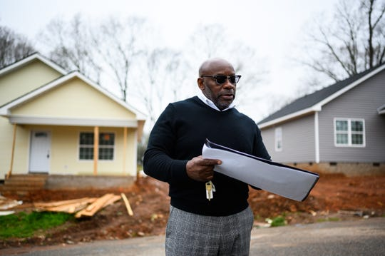 Pastor Steve Watson of New Jerusalem Baptist Church looks at plans for an upcoming apartment complex as he stands in front of two of the church's new affordable houses in Greer Tuesday, March 17, 2020.