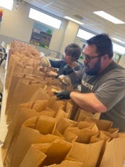 Staff at Project Host making bag lunches Tuesday, March 17, 2020, for kids who have been kept home from school as a result of the coronavirus outbreak.