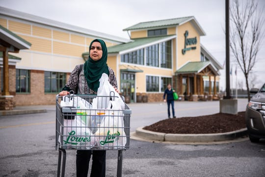 Fareeha Munawar walks groceries to be donated to Greer Relief & Resources Agency, to her car after shopping with her son Wajih Qazi at Lowes Foods in Greer, in response to the coronavirus outbreak Tuesday, March 17, 2020.