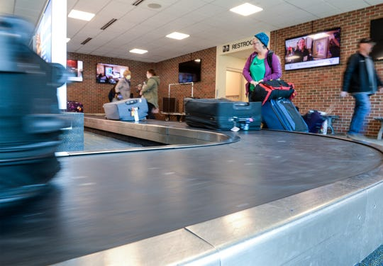 Passengers pick up their luggage from the baggage claim at Great Falls International Airport on Tuesday afternoon.