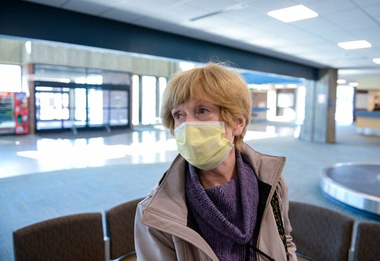 Traveler Caralee Cheney picks up her bags on Tuesday afternoon after arriving in Great Falls from Seattle to visit family.  She says she wears a medical mask because she suffers from a respiratory illness which makes her more vulnerable to the coronavirus.