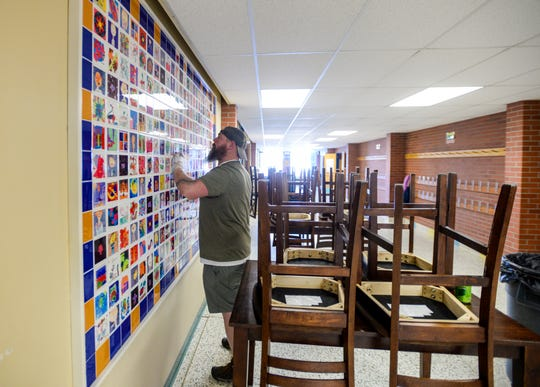 Justus Hilbig, second engineer at Sunnyside Elementary School, disinfects the walls at the school on Tuesday morning.