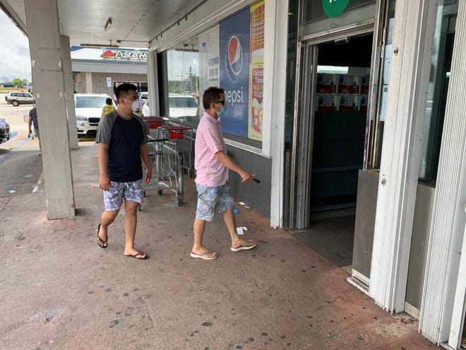 Customers wearing masks enter American Grocery in Dededo. The store requires all customers to be masked and employees turn away unmasked people at the entrance.