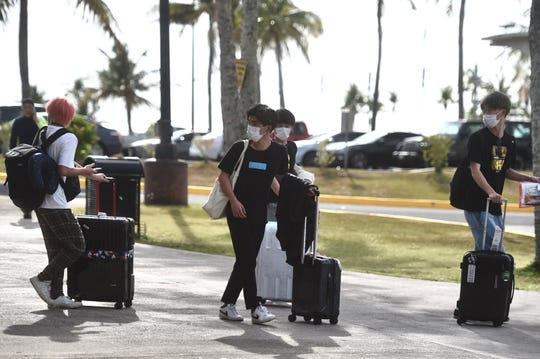 Passengers wearing face masks arrive at the A.B. Won Pat International Airport in Tamuning, March 17, 2020.