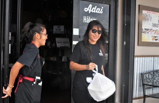 Veronica Dydasco, a server at Pika's Cafe, opens the door for customer Justine Perez on March 18 at the Upper Tumon restaurant. Pika's Cafe and several other restaurants have adjusted their business routines as a safety precaution.