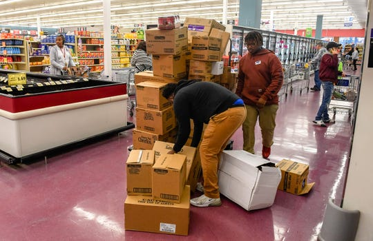 Store stockers struggle to keep up Monday as shoppers crowd the Sureway market on South Green Street. Customers were stocking up on supplies as the coronavirus pandemic spreading across the nation forced restaurants and bars to close.