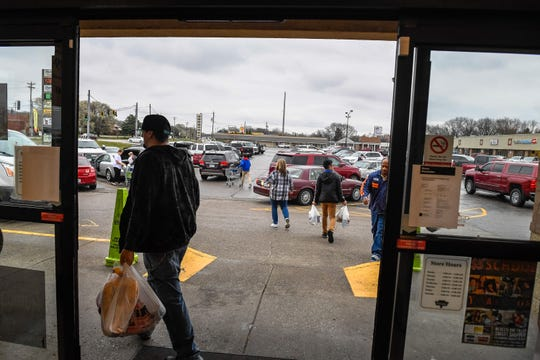 Shoppers head out into a packed parking lot as people crowd the Sureway Eastgate market on Monday after the governor issued a notice closing restaurants and bars to inside service.