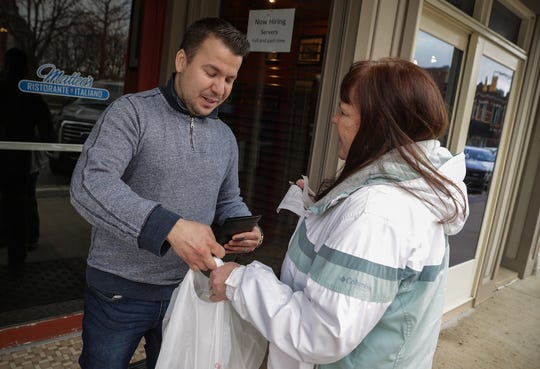 Lee Graham picks up a food order from Adson Franco outside Matteo's Ristorante Italiano in Noblesville. Like many Indiana restaurants, Matteo's will continue to fill carryout orders until restrictions on dine-in service at Indiana bars and restaurants are lifted. The restrictions aim to limit the spread of coronavirus.