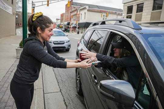 Owner Robyn Littler hands a curbside carryout order to Jennifer Hatcher, Pat Hatcher and their dog Lilly outside Noble Coffee & Tea Company in Noblesville on March 17, 2020.