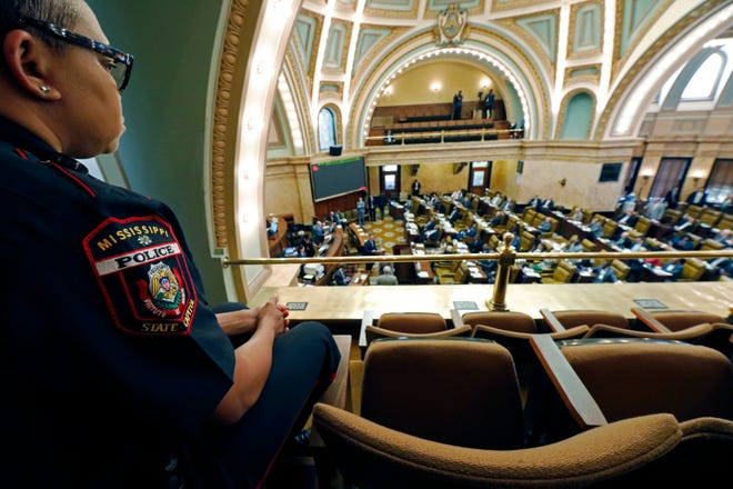 Capitol Police officer Lykesia Smith observes the House chamber in a nearly empty gallery at the Capitol in Jackson, Miss., Tuesday, March 17, 2020. Visitors, lobbyists, tour groups were discouraged from entering the building as lawmakers are working on legislation that would temporarily suspend their business and grant administrative pay to some local governmental entities. (