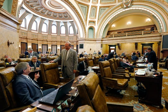 A nearly empty gallery hangs over House members in their chamber as they chat among themselves while waiting for a bill that would temporarily suspend their business and grant administrative pay to some local governmental entities Tuesday, March 17, 2020, in Jackson, Miss.