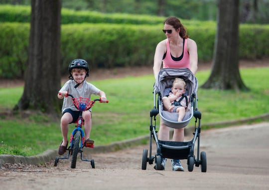 Pushing her daughter Betsy, 1, and walking beside her son, John Owen, 6, Sarah Compton, of Madison, gets some fresh air with her children Tuesday, March 17, 2020. Compton, a physical therapist for Jackson Public Schools is home because of the JPS closure due to the coronavirus.