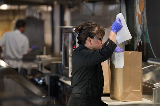 Anjanette Hile prepares a to-go order at Litton's Market and Restaurant in Knoxville, Tennessee on Tuesday, March 17, 2020. Litton's has dropped prices by 20% to keep on staff, has switched to throw-away menus cards, disposable silverware and condiments and cleans surfaces like the entrance every 30 minutes to combat the spread of the coronavirus.