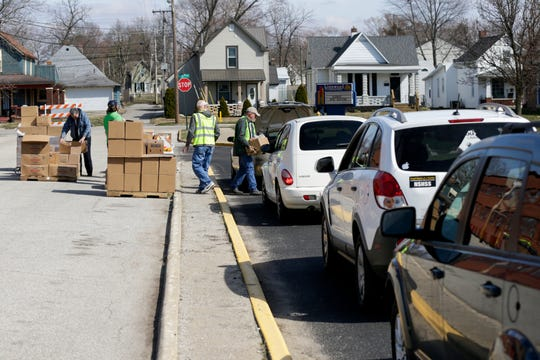 Food Finders Food Bank volunteers load cars at a drive-thru pantry outside of Linwood Elementary School, Tuesday, March 17, 2020 in Lafayette.