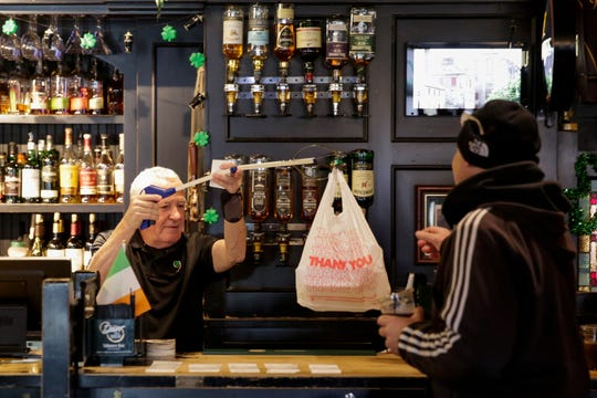 Owner Jerry O'Bryan hands a customer their order from behind the Nine Irish Brothers bar, Tuesday, March 17, 2020 in West Lafayette.