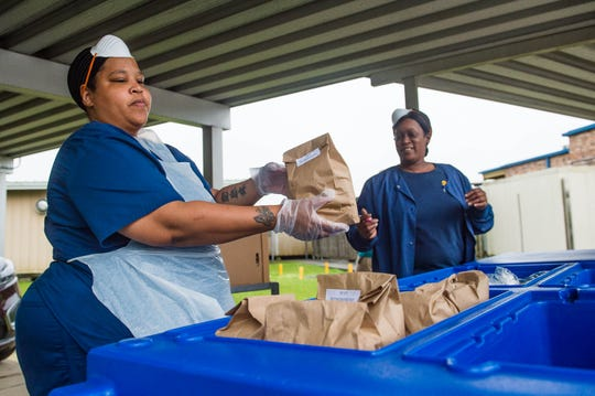 Gayelyn Thibeaux and Titanique LeBlanc serve meals to students in at Cpl. Michael Middlebrook Elementary Tuesday, March 17, 2020.